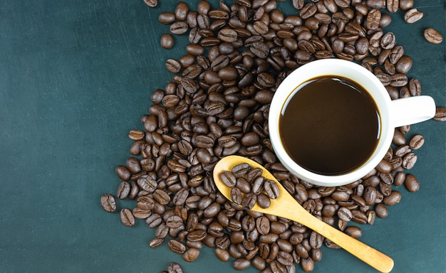 Koffie in een witte koffiekopje op een koffieboon en een houten lepel op een houten tafel