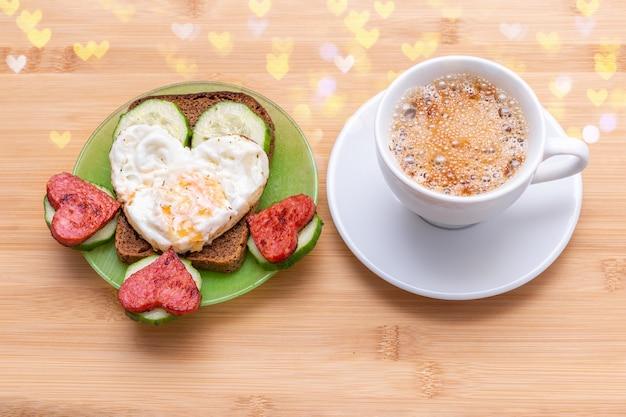 Koffie in een witte kop en een broodje met hartvormige gebakken eieren, worstjes en komkommers op een groene plaat op een houten ondergrond met bokeh, bovenaanzicht. valentijnsontbijt