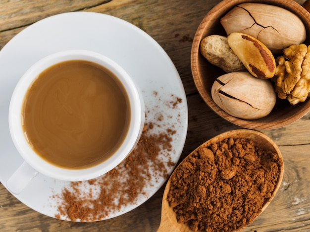 Koffie in een witte kop, noten en cacao in een lepel op een houten tafel.