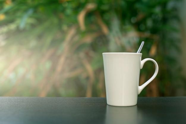 Koffie in een witte kop op de lijst in de tuin