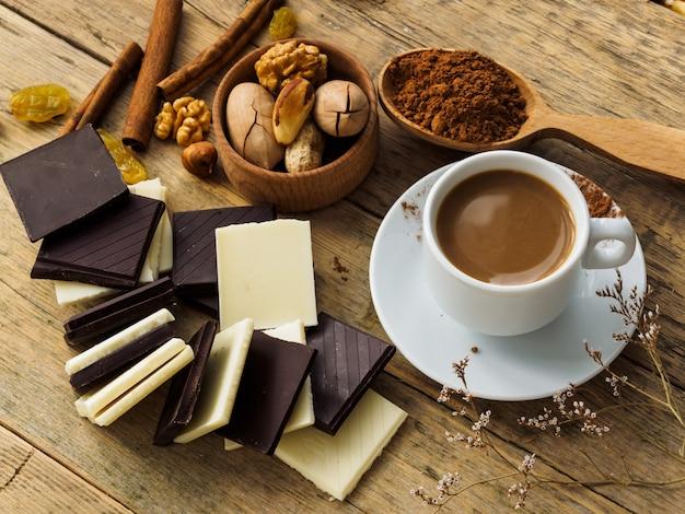 Koffie in een witte kop op een houten tafel, omringd door chocolade en noten.