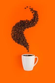 Koffie in een witte kop op een oranje oppervlak met koffiebonen.