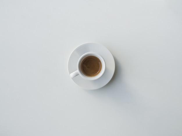 Koffie in een witte kop staat op een witte tafel.