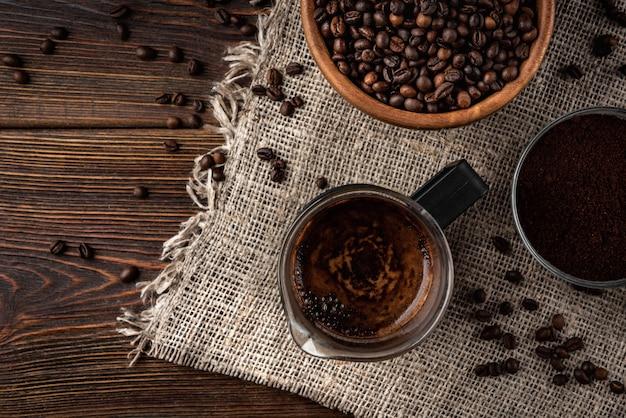 Koffie in franse pers, koffiebonen en poeder op donkere houten achtergrond.
