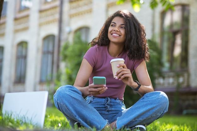 Koffie in het park. een schattig meisje in een roze t-shirt dat op het gras zit en koffie drinkt