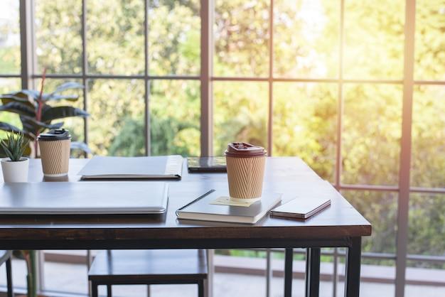 Koffie in papieren beker, laptop en notitieblok op houten tafel in kantoor