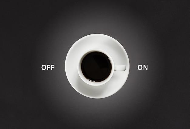 Koffie in witte kop met een belettering aan en uit op zwarte leisteen achtergrond