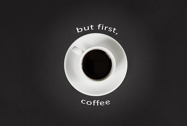 Koffie in witte kop met een belettering maar eerste koffie op zwarte leisteen achtergrond