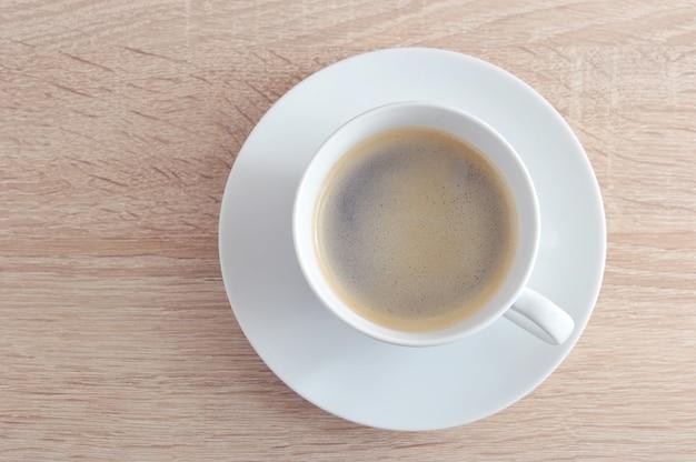 Koffie in witte kop met schotel op een houten achtergrond