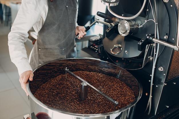 Koffie koeling in lege koffiebrander machine bij koffiebranderingsproces jonge vrouw werknemer giet gebrande koffiebonen