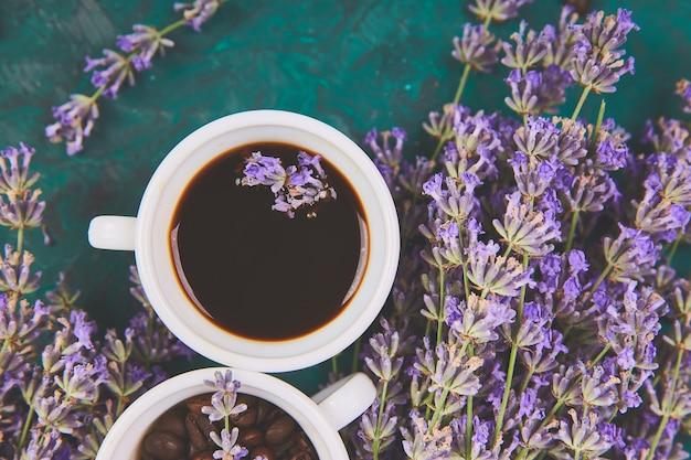 Koffie, koffieboon in kopjes en lavendel bloem op groene tafel van bovenaf. goedemorgen concept. vrouw bureau. gezellig ontbijt. mockup. plat lag stijl