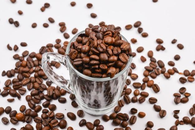 Koffie korrels worden gegoten in een glazen beker op een witte achtergrond
