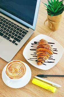 Koffie, laptop en croissants om een zakelijk ontbijt op de kantoortafel in de ochtend te laten zien.