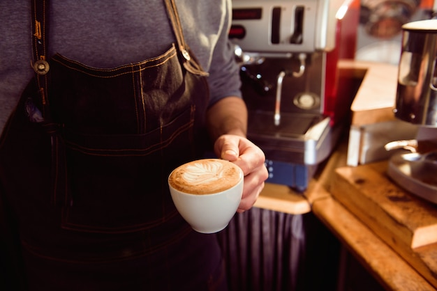 Koffie latte barista die patroon in een kop van koffiewinkel maakt.