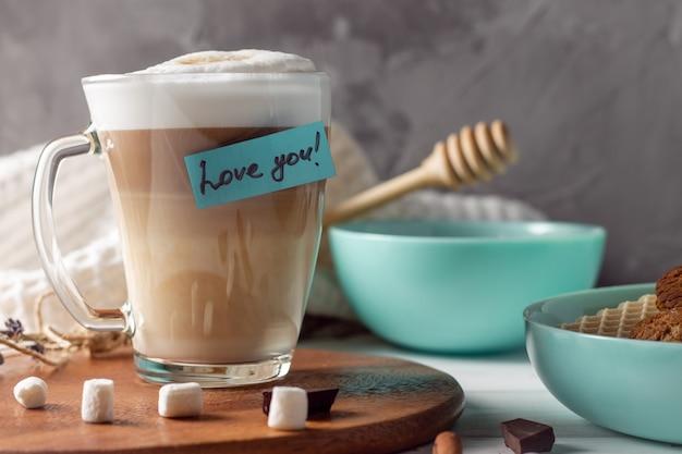 Koffie latte cup met love you sticker op houten dienblad met turquoise kommen met koekjes en marshmallows op grijs muuroppervlak