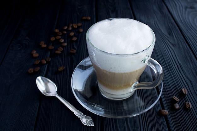 Koffie latte in de glazen beker op de zwarte houten tafel