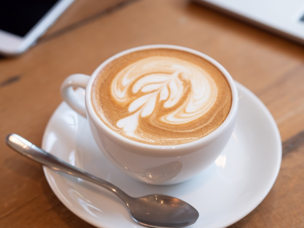 Koffie latte in een witte kop op houten lijst in koffiewinkel.