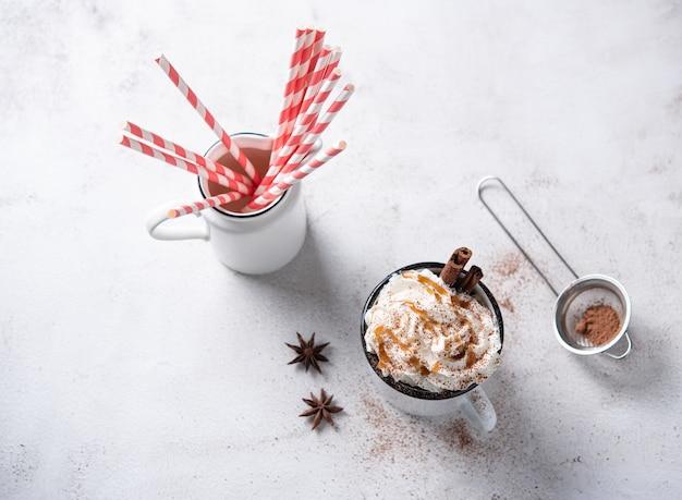 Koffie latte met karamelcrème, rode papieren buis en kaneel in een witte mok op een witte tafel
