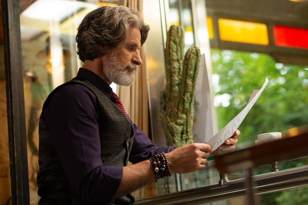 Koffie liefhebber. geconcentreerde cafébezoeker die aan tafel zit en een menu leest dat koffiedrank kiest.