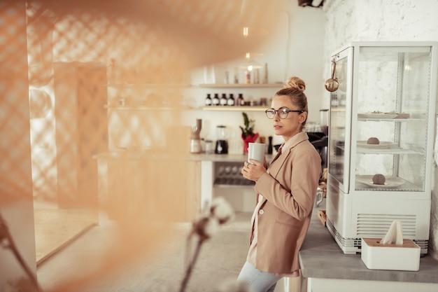 Koffie liefhebber. mooie vrouw die met een kopje koffie in de buurt van de koelkast staat en nadenkt over haar nieuwe project.