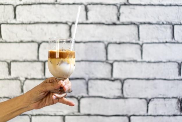 Koffie macchiato en melklaag met ijs in champagneglas werd door aziatische grootmoeder hand voor wit bakstenen muurbehang gehouden.