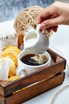 Koffie, melk en een bord koekjes.