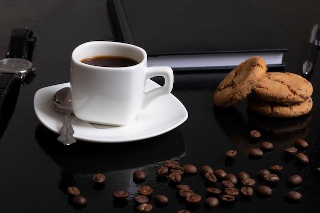 Koffie met bonen en witte kop. donkere sfeer en kopie ruimte. havermout cookies en notebook