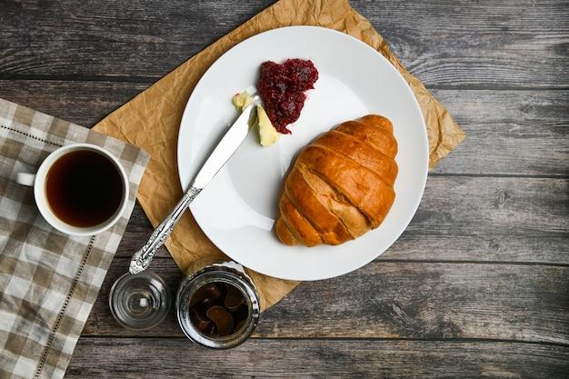 Koffie met een croissant. het begin van de ochtend. een kop koffie. verse franse croissant. koffiekopje en vers gebakken croissants op een houten. .