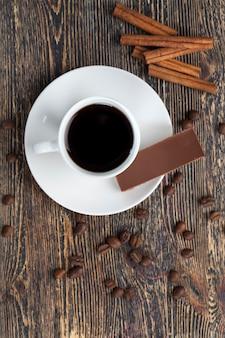 Koffie met een mok en melkchocolade, dessert gemaakt van koffie en cacaosnoepjes, zoete chocolade gemaakt van cacao en suiker met warme koffie, close-up