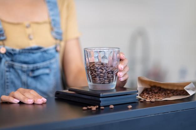 Koffie met hele bonen. dames hand zetten een glas met koffiebonen op schalen op teller, geen gezicht is zichtbaar
