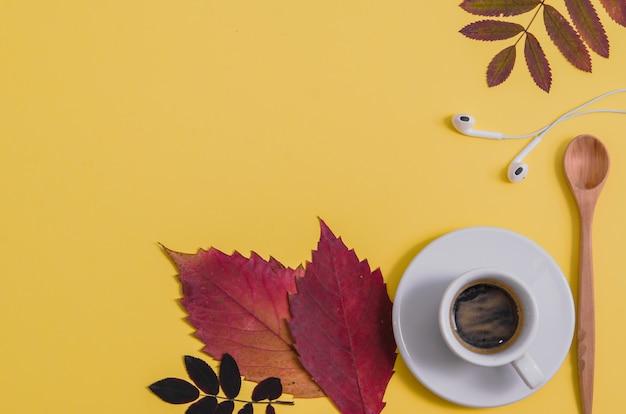 Koffie met herbarium en koptelefoon op gele achtergrond. herfst.