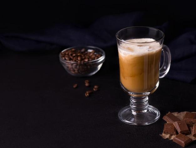 Koffie met ijs, karamel en room op een zwarte achtergrond