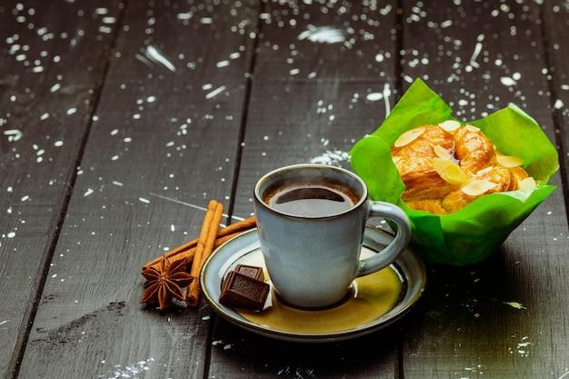 Koffie met kaneel en cake op een zwarte houten tafel