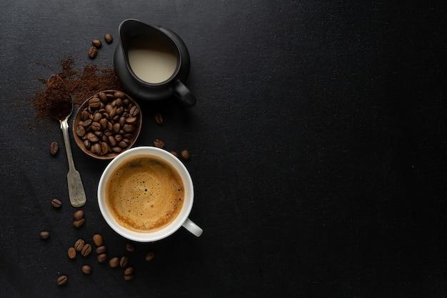 Koffie met koffiebonen, koffie en lepel op donker