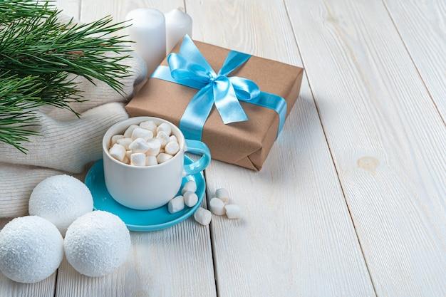 Koffie met marshmallows, dennentakken en kerstballen op een lichte achtergrond met ruimte om te kopiëren