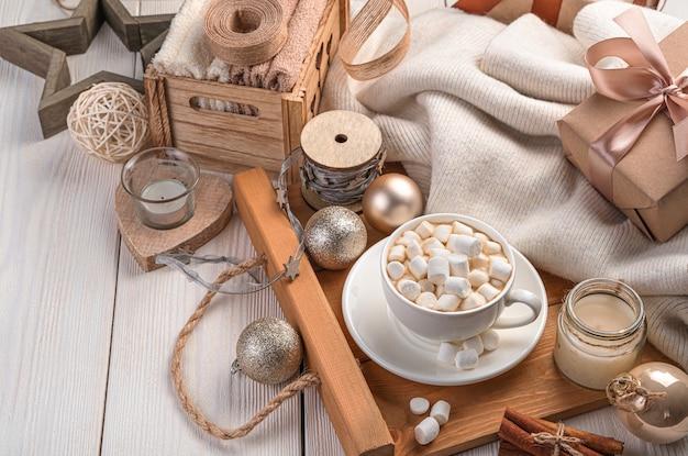 Koffie met marshmallows, een geschenkdoos en kerstversiering op een delicate lichte achtergrond. het concept van kerstmis en nieuwjaar. zijaanzicht, kopieer ruimte.