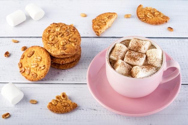 Koffie met marshmallows in een roze mok en koekjes op een witte houten tafel