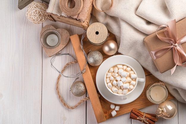 Koffie met marshmallows op een kerstachtergrond met een cadeau en kerstversiering. bovenaanzicht, kopieer ruimte.
