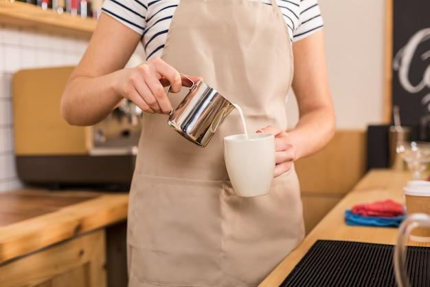 Koffie met melk. close-up van melk die in de beker wordt gegoten door een prettige, bekwame vrouw terwijl ze in de coffeeshop aan het werk was