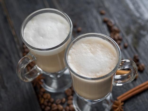 Koffie met melk in een glas op donkere houten achtergrond