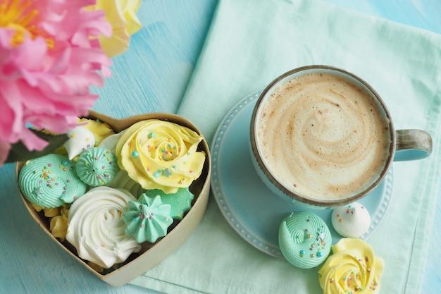 Koffie met melkschuim in een blauwe kop en een hartvormige doos gevuld met veelkleurige schuimgebakjes.