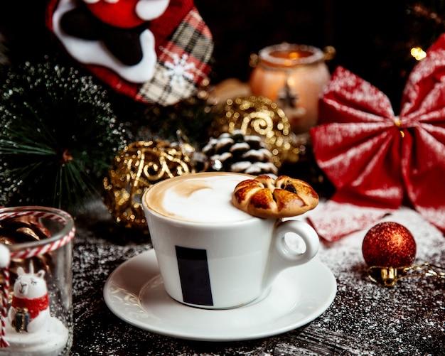 Koffie met opgeklopte melk en koekje