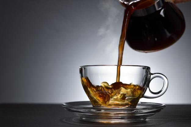 Koffie met rook gieten op een transparante beker op zwarte achtergrond