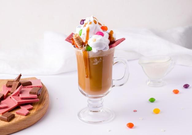 Koffie met room en karamel versierd met snoep en chocolade op een witte achtergrond