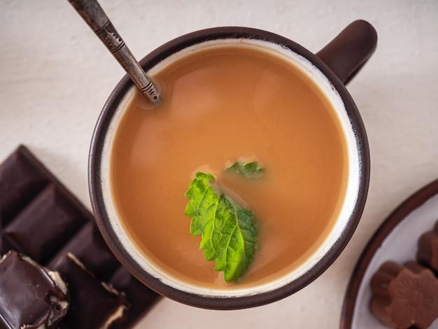 Koffie met room en munt in een bruine keramische mok, chocolaatjes en snoepjes op een wit tafelblad