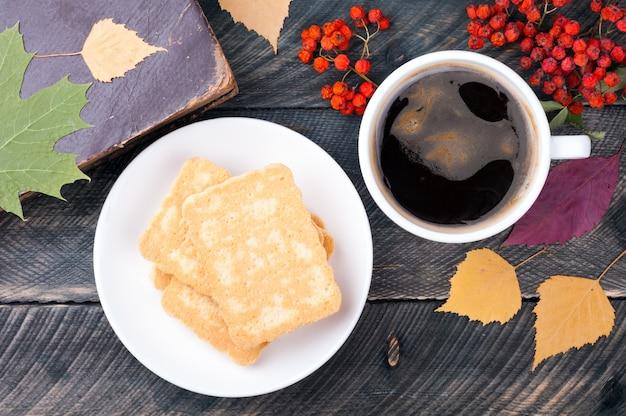 Koffie met schuim, een bord koekjes, oud boek, herfstbladeren en gedroogde lijsterbes op houten achtergrond