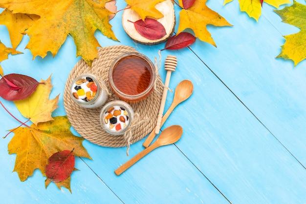Koffie met yoghurt op tafel met herfstbladeren