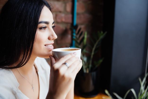 Koffie. mooi meisje, het drinken van thee of koffie in cafe. schoonheid model vrouw met de kop warme drank. warme kleuren afgezwakt