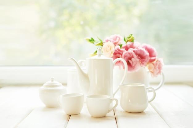 Koffie naast een vaas met bloemen op een tafel tegen een raam