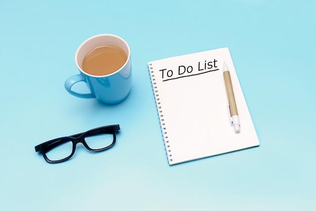 Koffie, notitieboekje en glazen op blauwe achtergrond